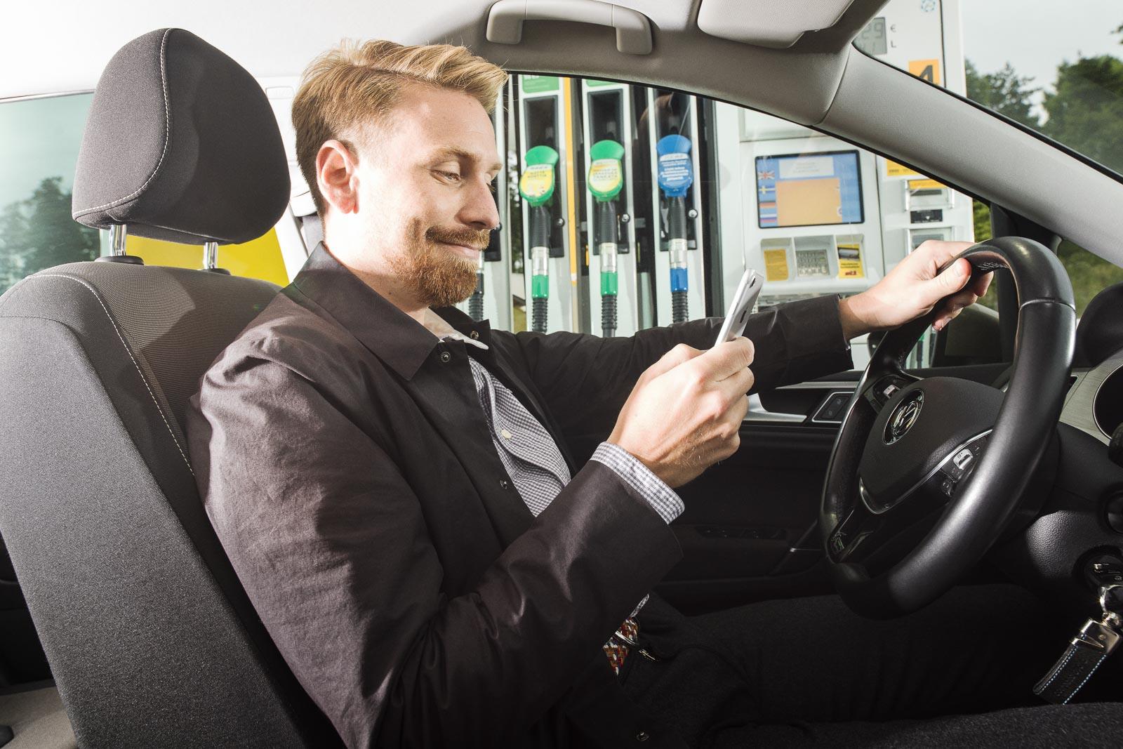 mies käyttää st1 way sovellusta autossa istuessaan