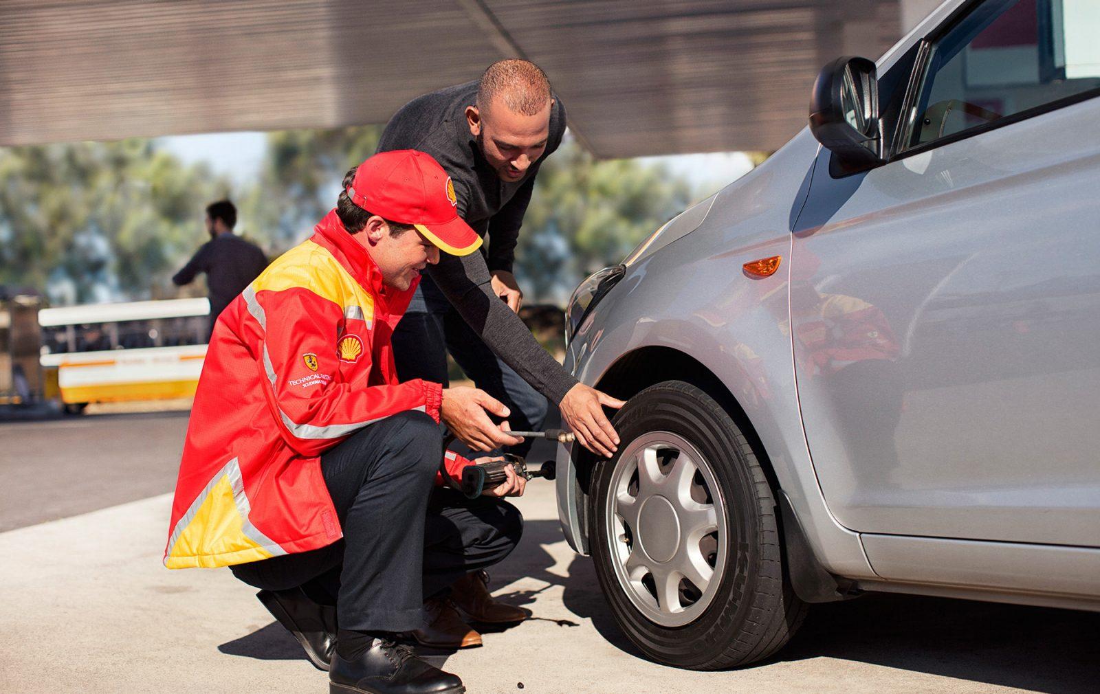 palvelumestari tarkastamassa rengaspaineita henkilöautosta shell-asemalla