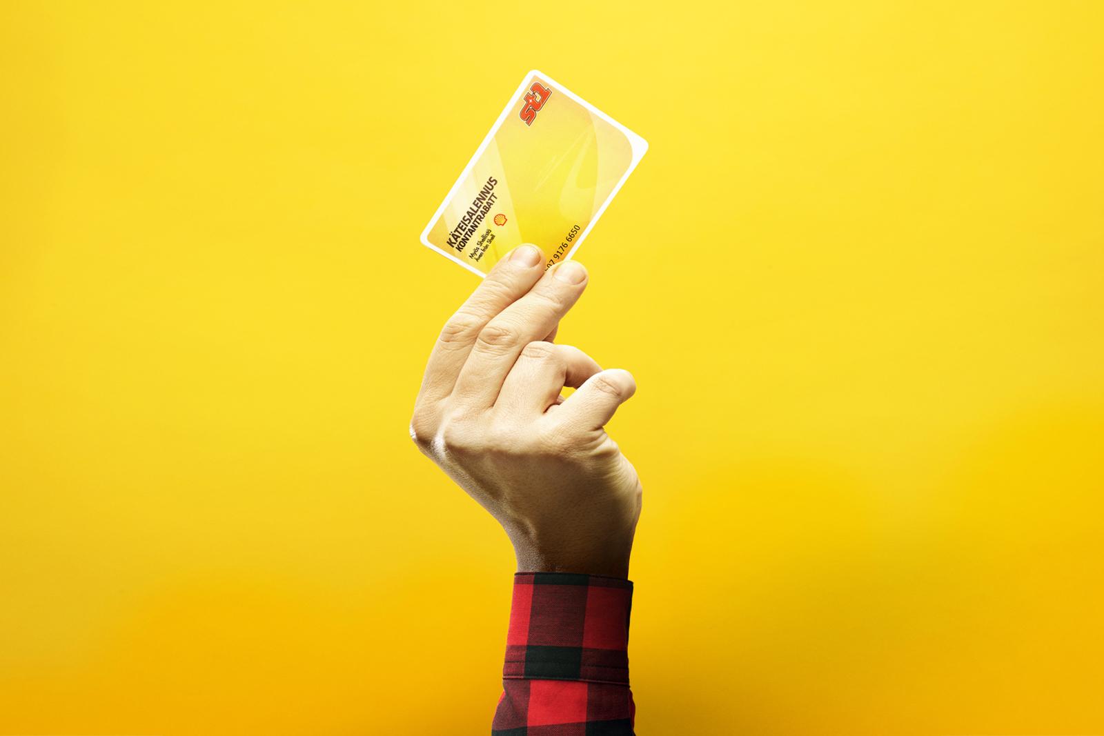 Mies_pitelee_Käteisalennuskorttia_kädessään