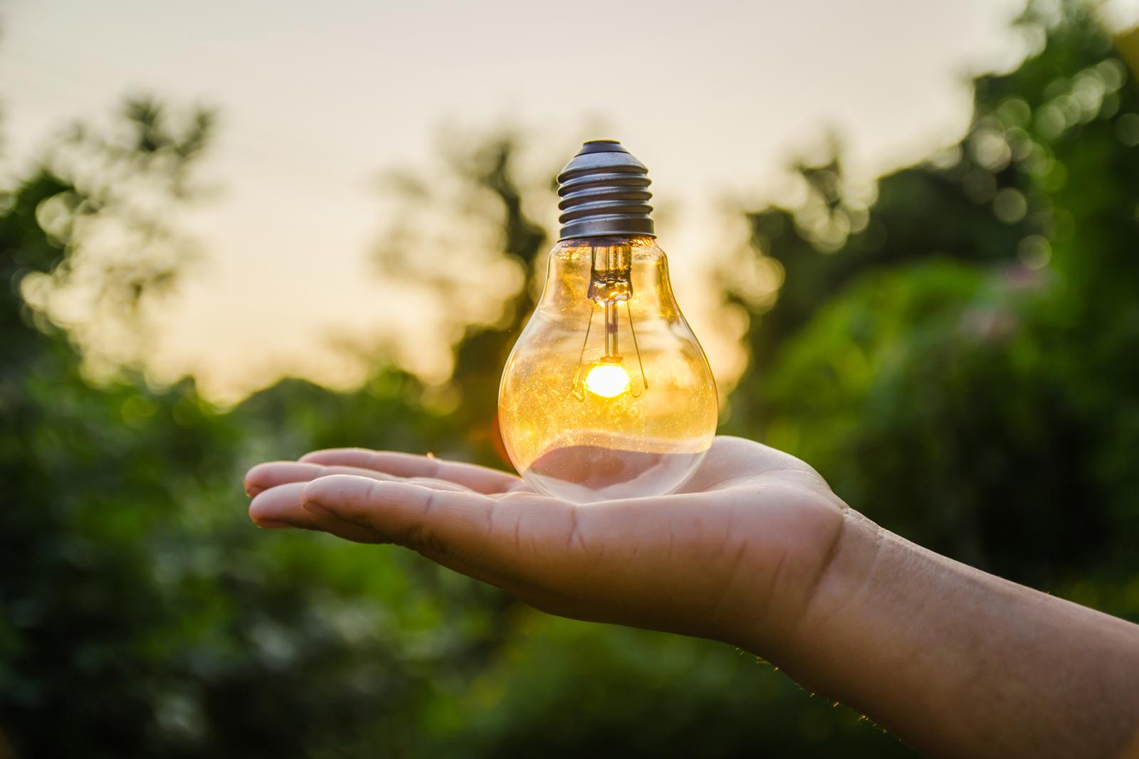En hand som håller en i en lysande glödlampa