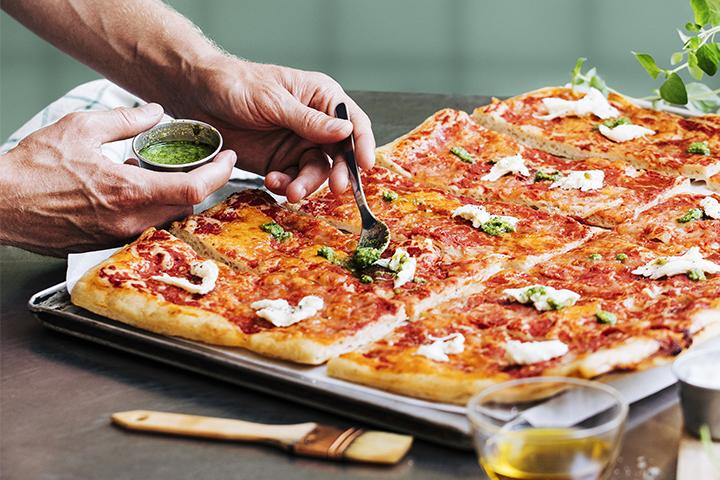 Surdegspizza med soltorkad tomatcrème och grillad zucchini toppad med mozzarella och ruccola.