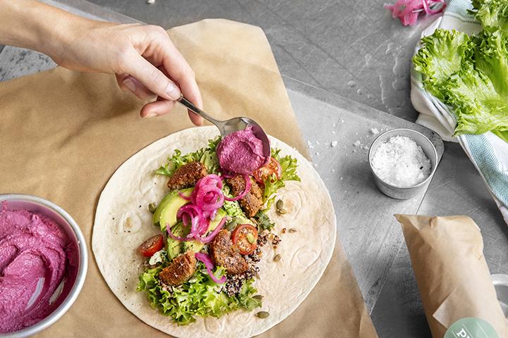 Wrap med kyckling, knaprigt bacon och picklad rödlök på en bädd av grönkål och quinoa.