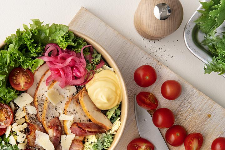 Matig kycklingsallad med quinoa, frasig bacon, tomater och krämig dressing.